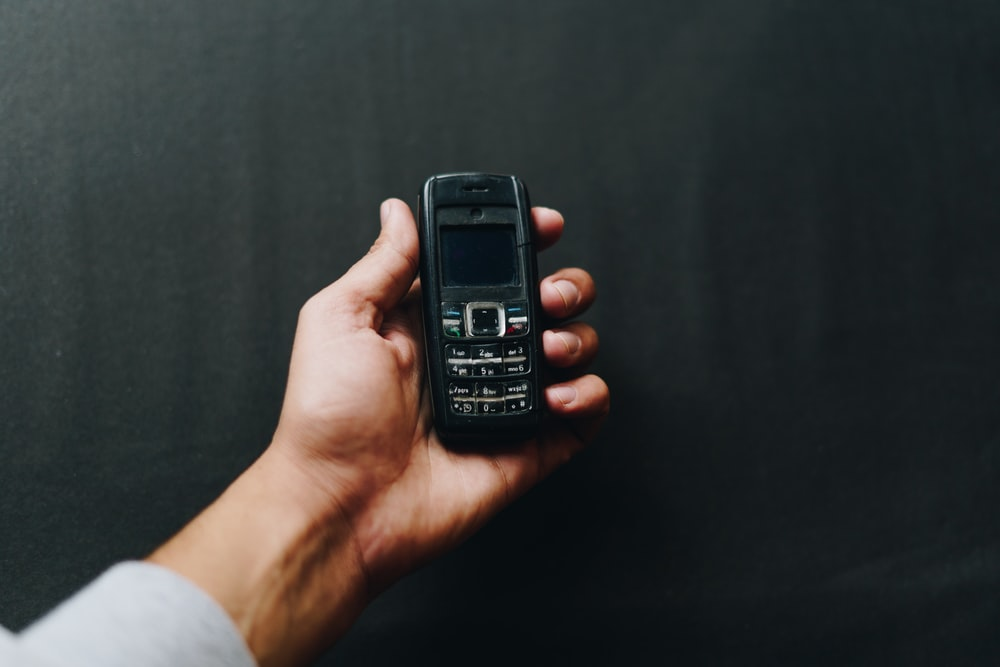 person holding black nokia candy bar phone