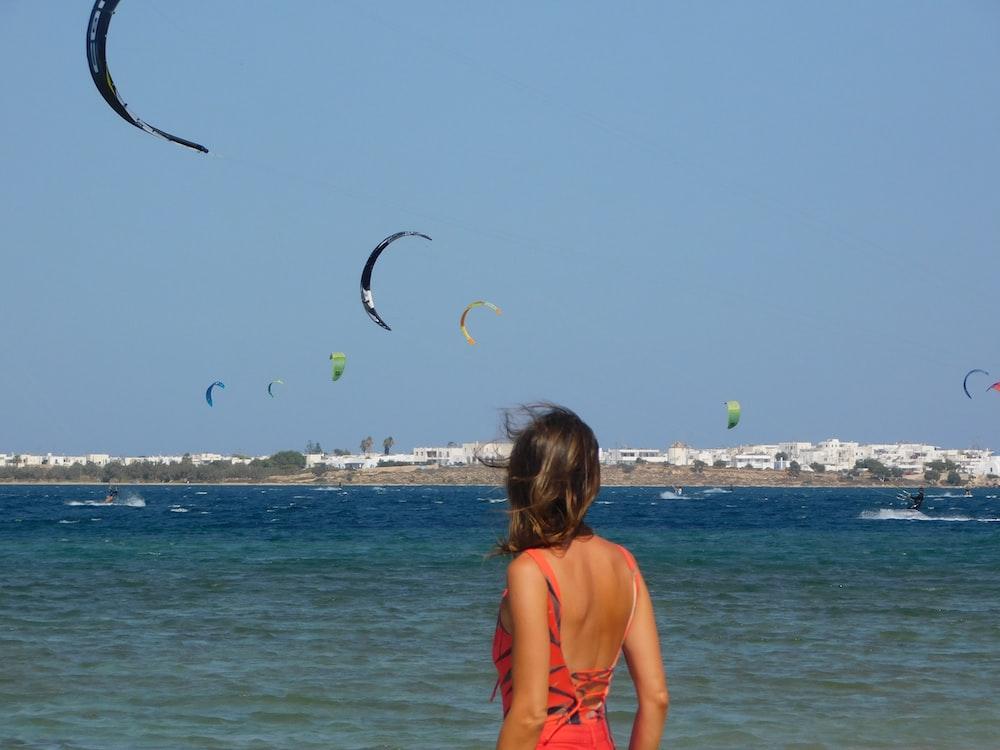 woman in orange bikini top holding black bird flying over the sea during daytime