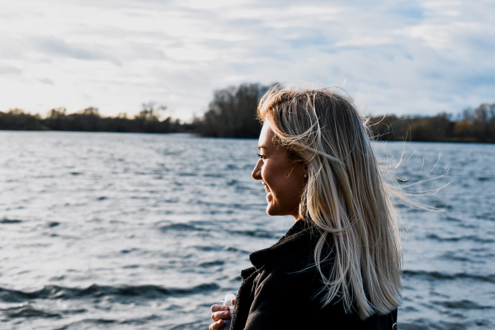 woman in black jacket standing near body of water during daytime