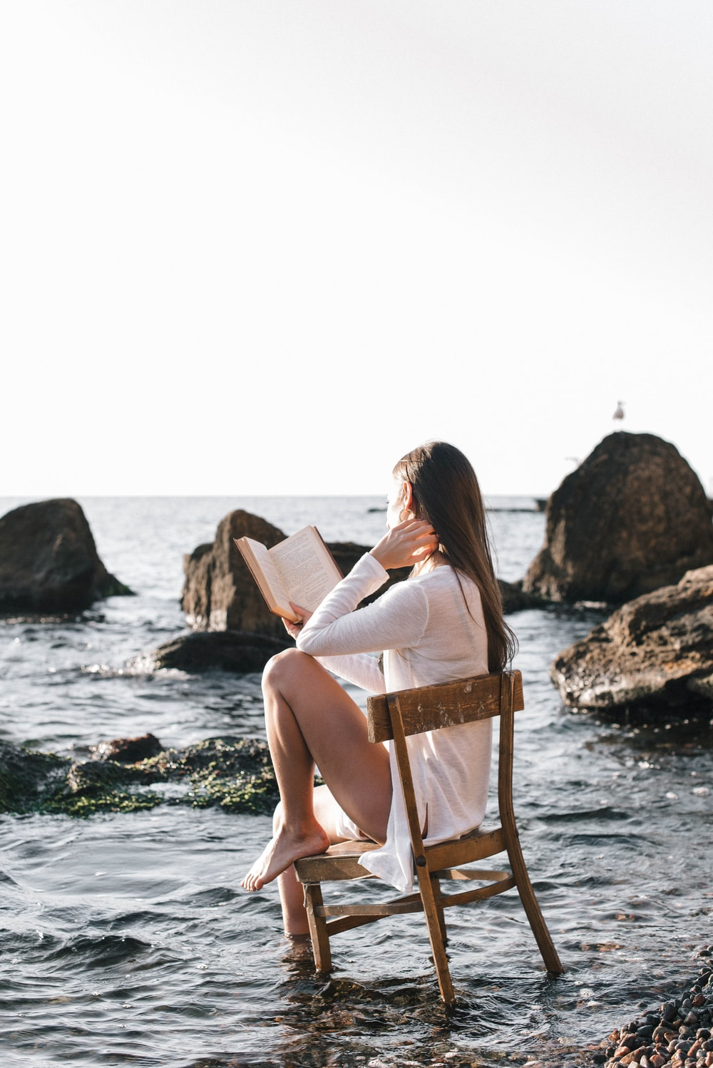 woman in white dress sitting on brown wooden chair reading book on beach during daytime