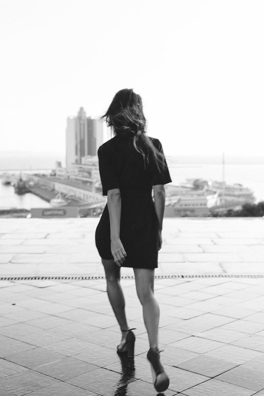 woman in black dress walking on sidewalk during daytime