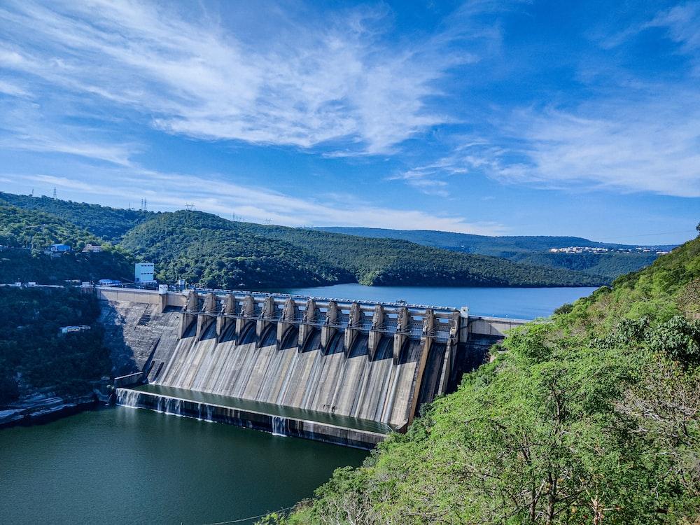 gray concrete dam under blue sky during daytime
