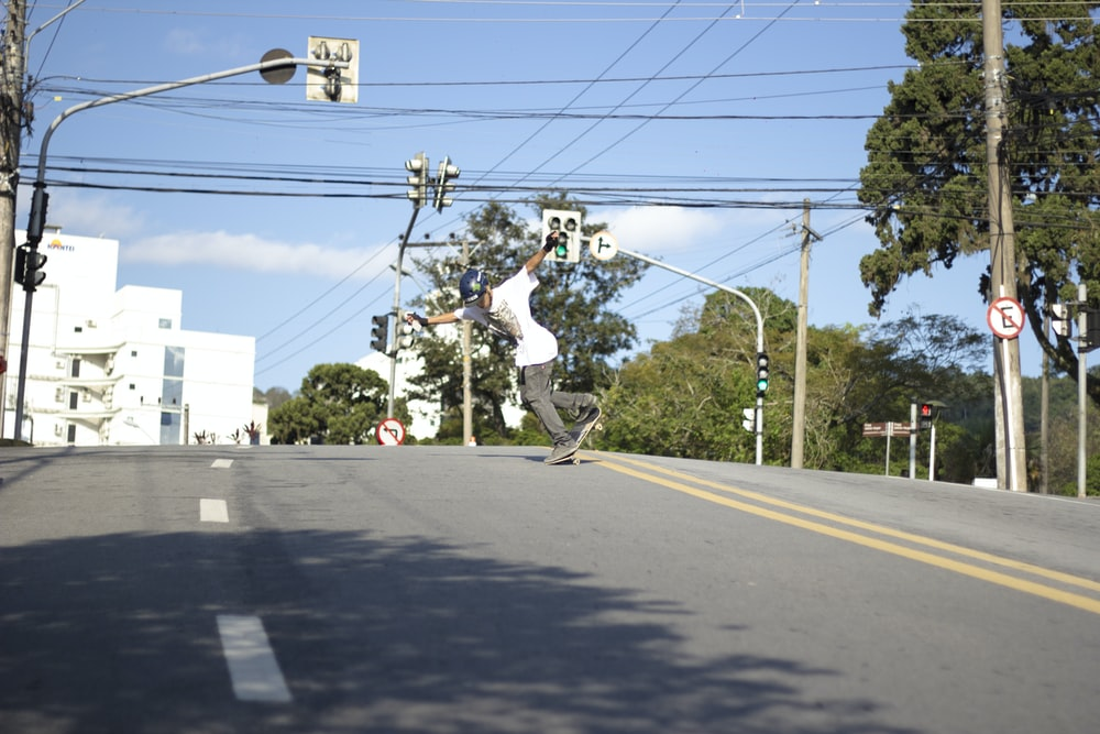 man in white shirt and black pants riding on black skateboard during daytime
