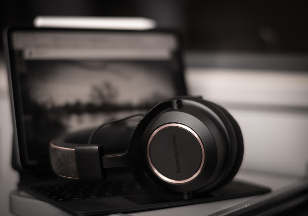 black and silver headphones on black laptop computer