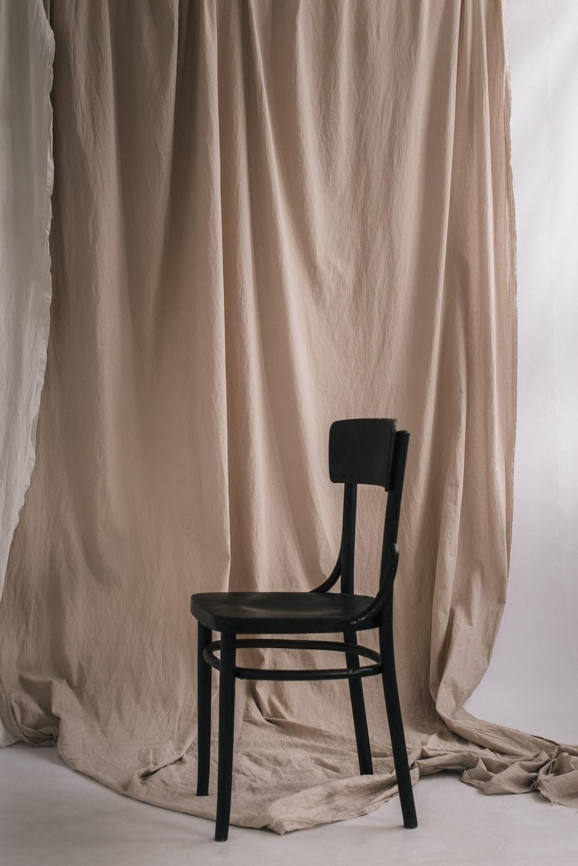 black wooden chair beside white curtain