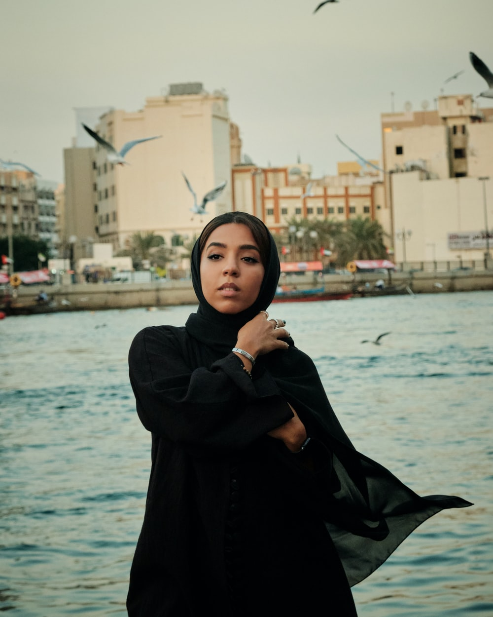 woman in black hijab standing near body of water during daytime