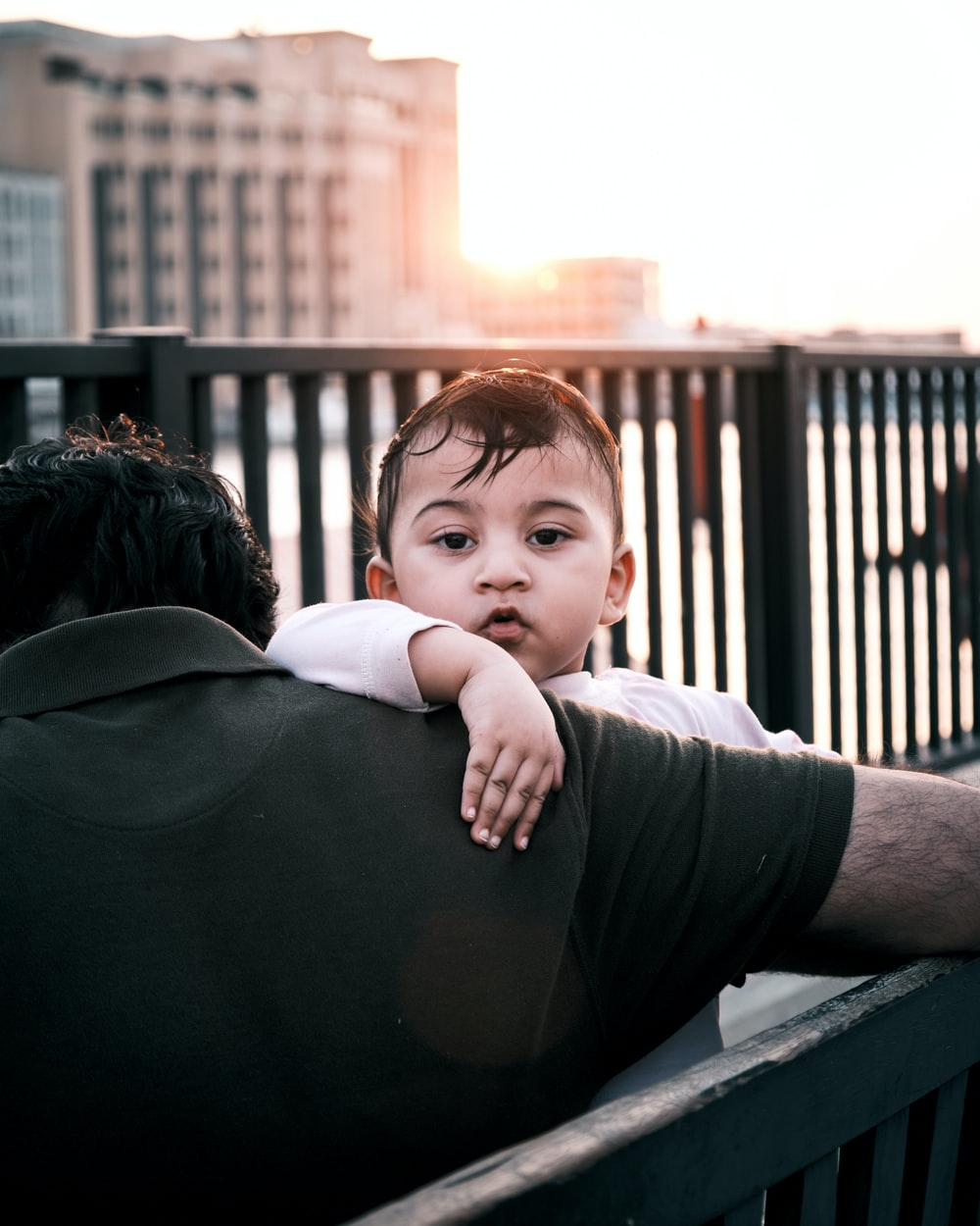 man in black t-shirt carrying baby in black onesie