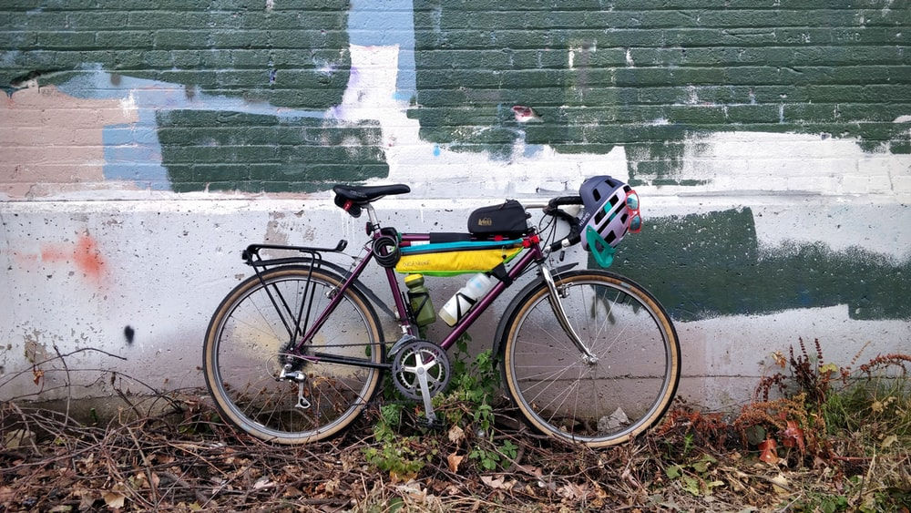 yellow and black road bike beside green wall