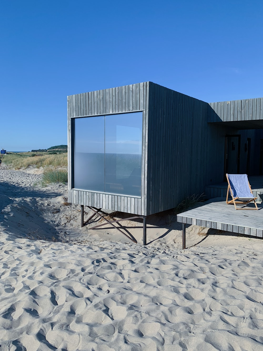 gray wooden house on brown sand during daytime