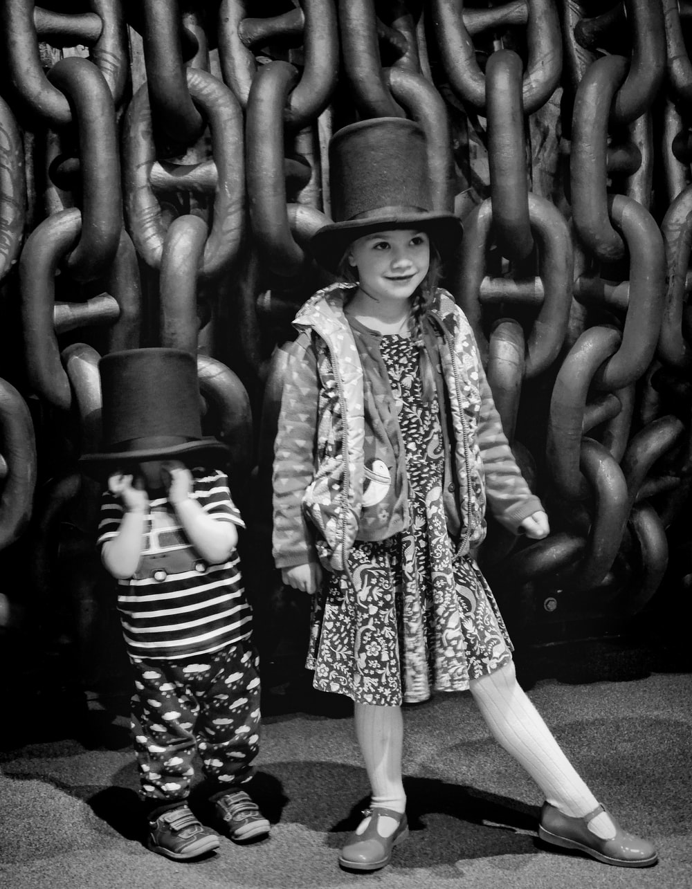 grayscale photo of girl in long sleeve dress and hat standing near metal chain link fence