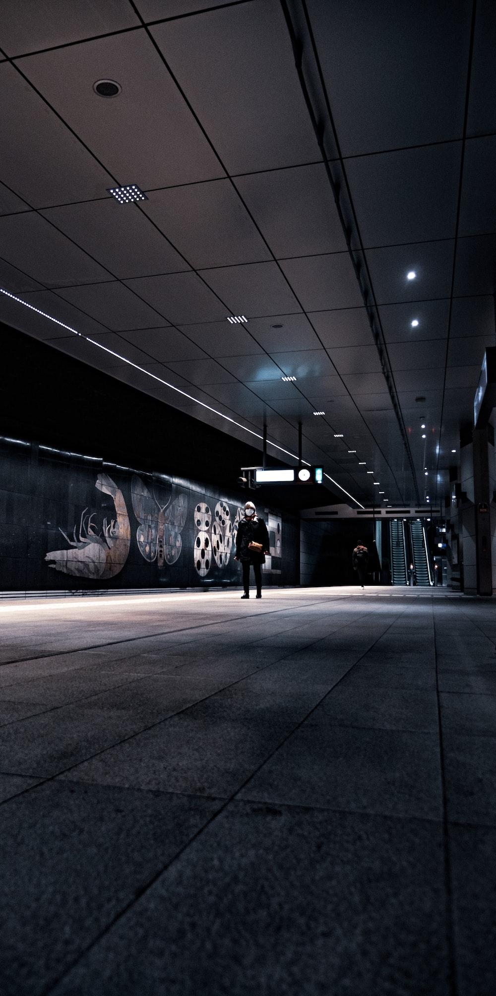 man in black jacket standing near wall