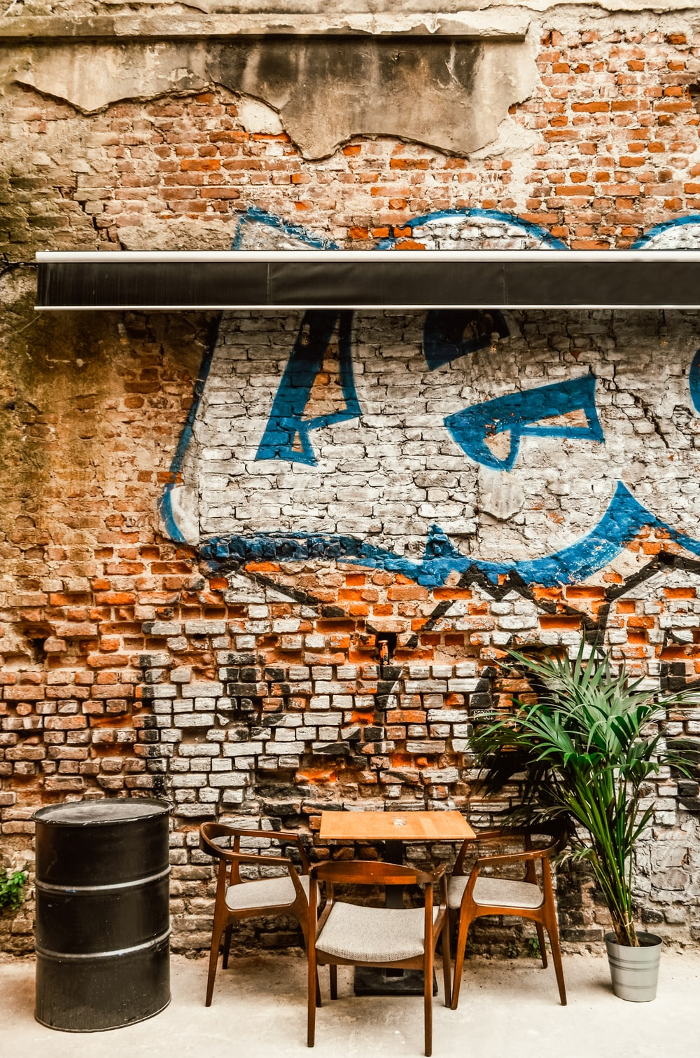 brown brick wall with blue and white graffiti