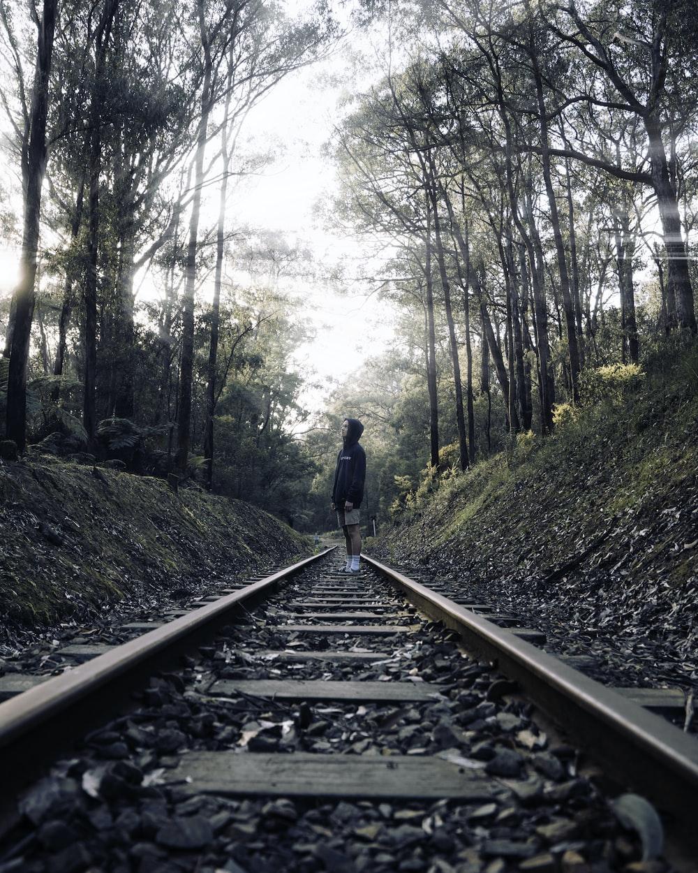 man in blue jacket walking on train rail during daytime