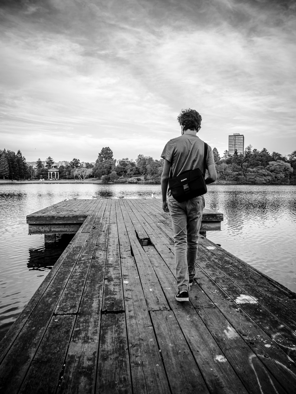 man in black jacket and pants standing on wooden dock in grayscale photography