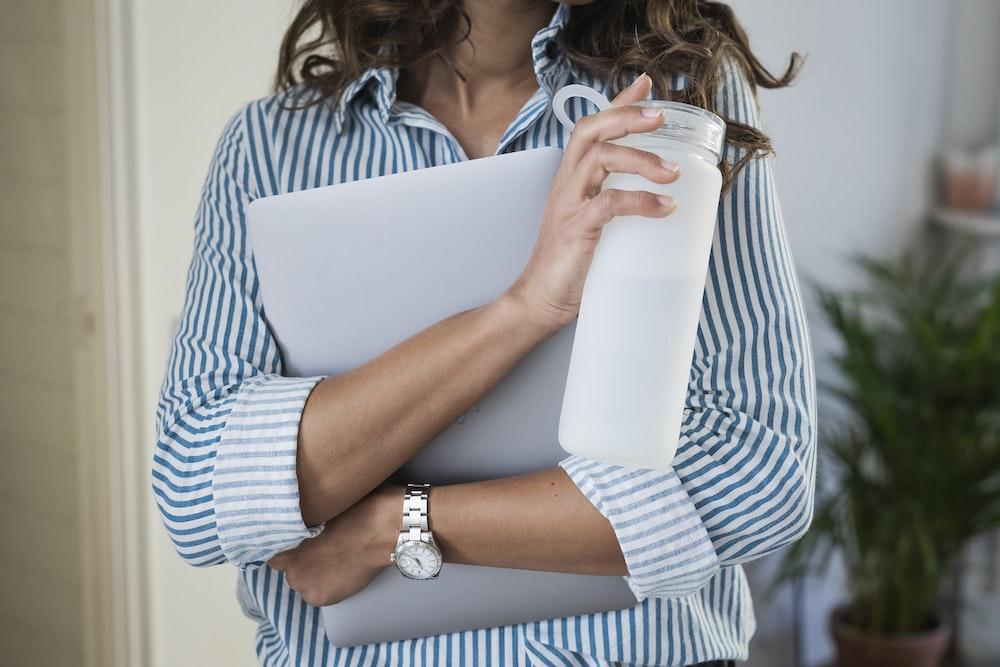 woman in white and blue stripe shirt holding white ceramic mug