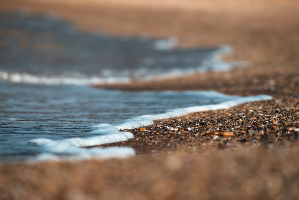 water waves on brown sand during daytime