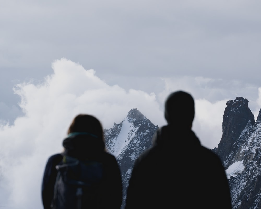 silhouette of 2 person standing on mountain during daytime