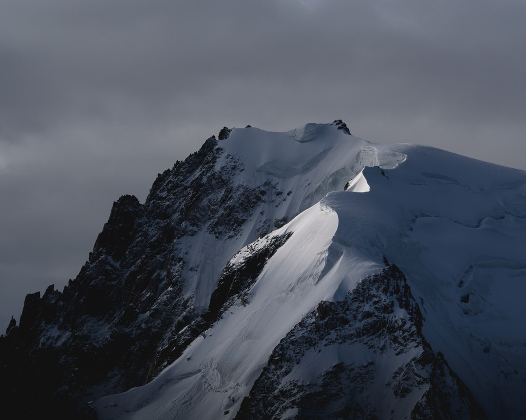 Snow Covered Mountain Under Cloudy Sky During Daytime - unsplash