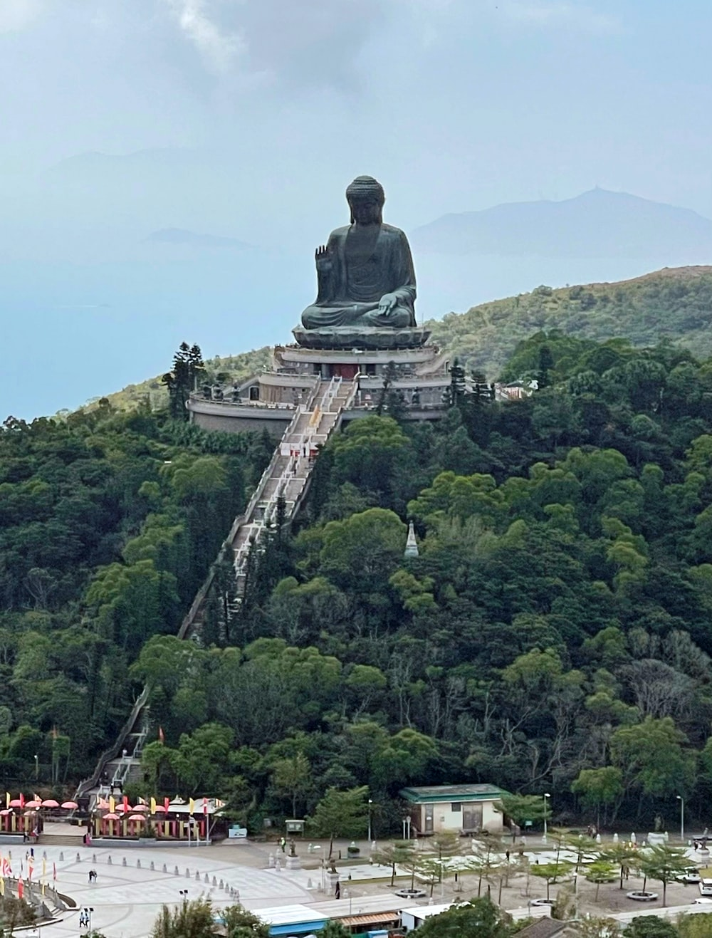 statue of man on top of mountain during daytime