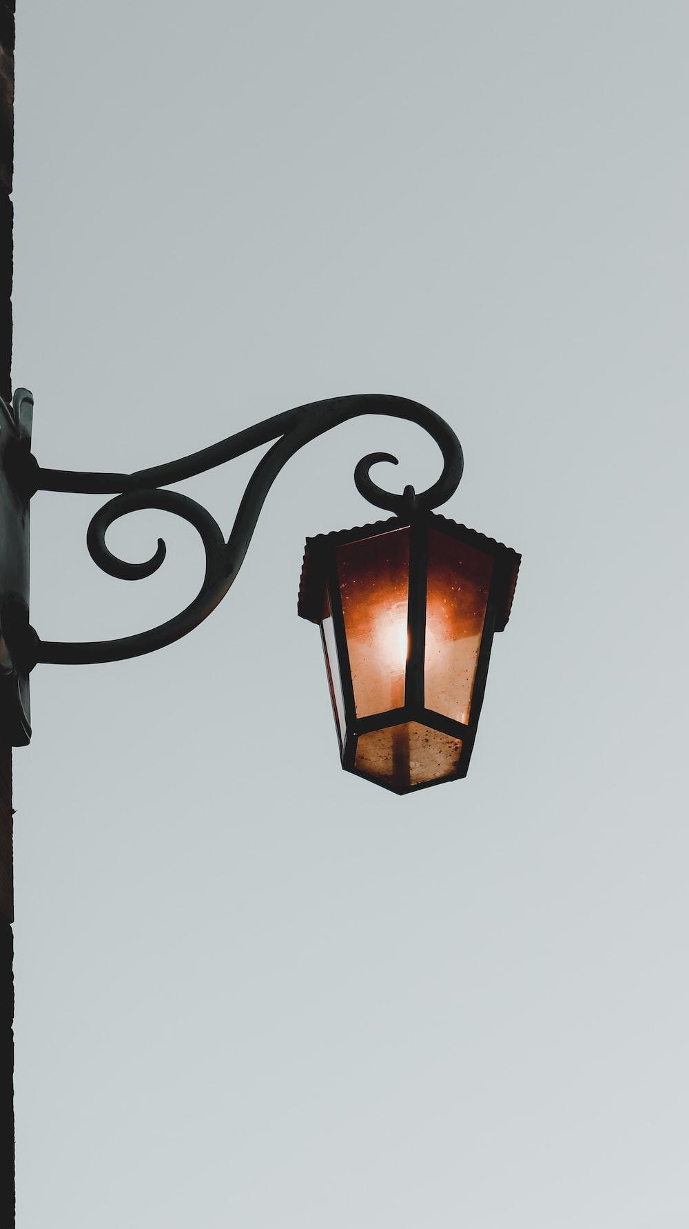 black metal frame lamp turned on during daytime
