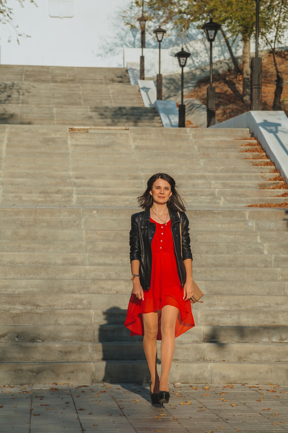woman in black and red dress standing on gray concrete stairs
