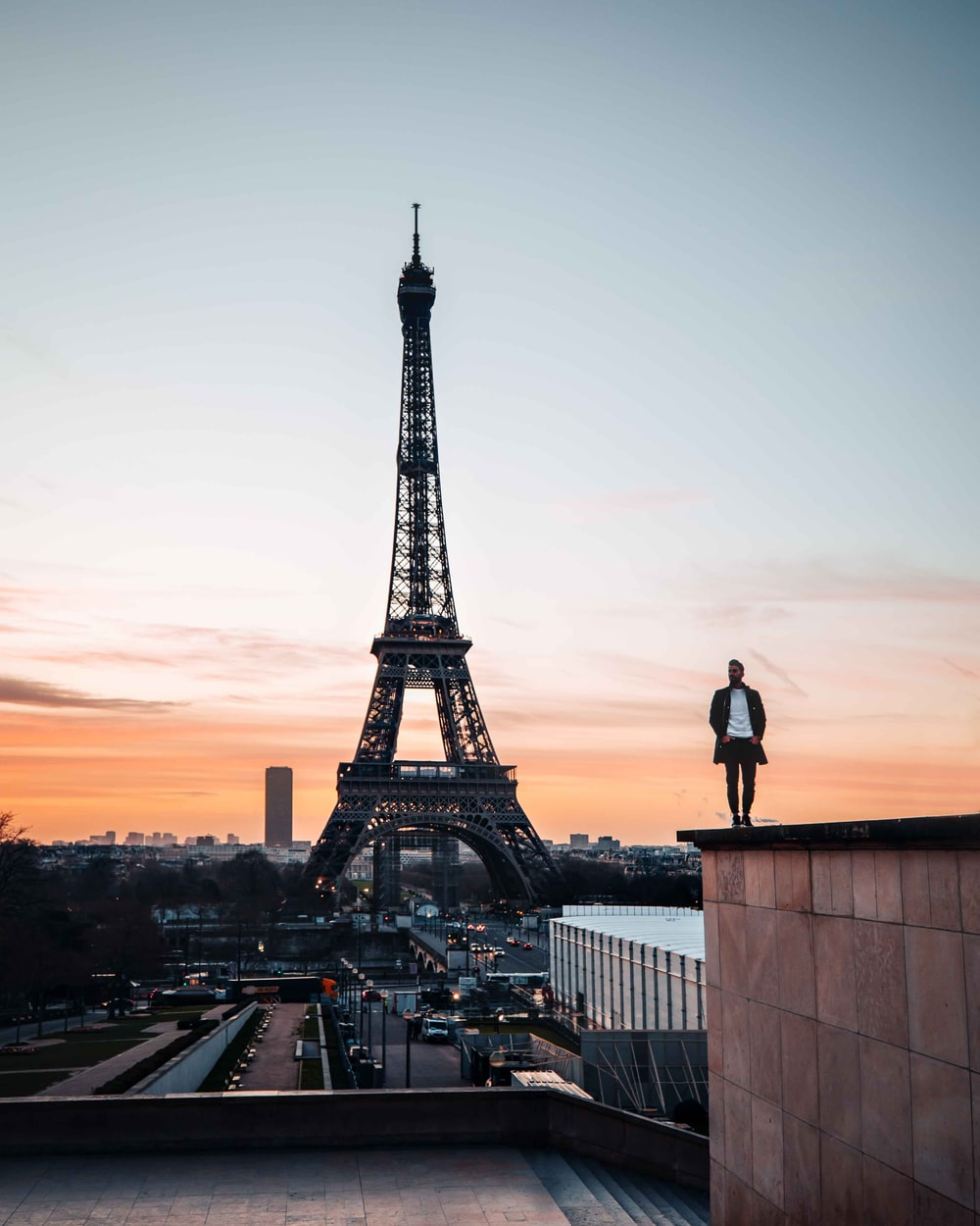 man in black jacket standing on top of building looking at eiffel tower during sunset