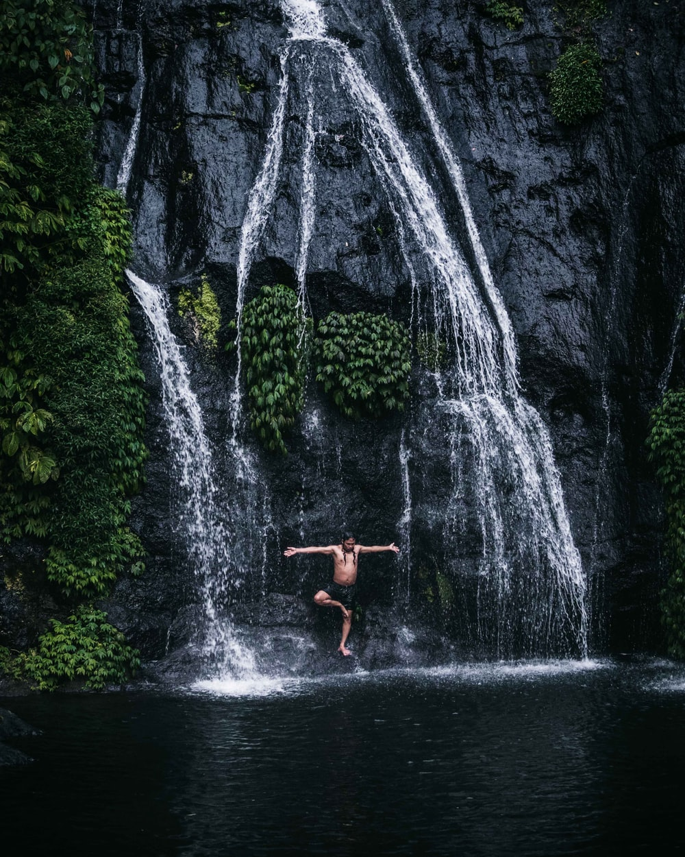 person in red shorts standing on rock in front of waterfalls during daytime