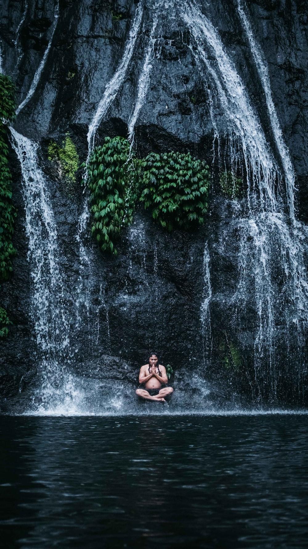 woman in black bikini sitting on water fountain