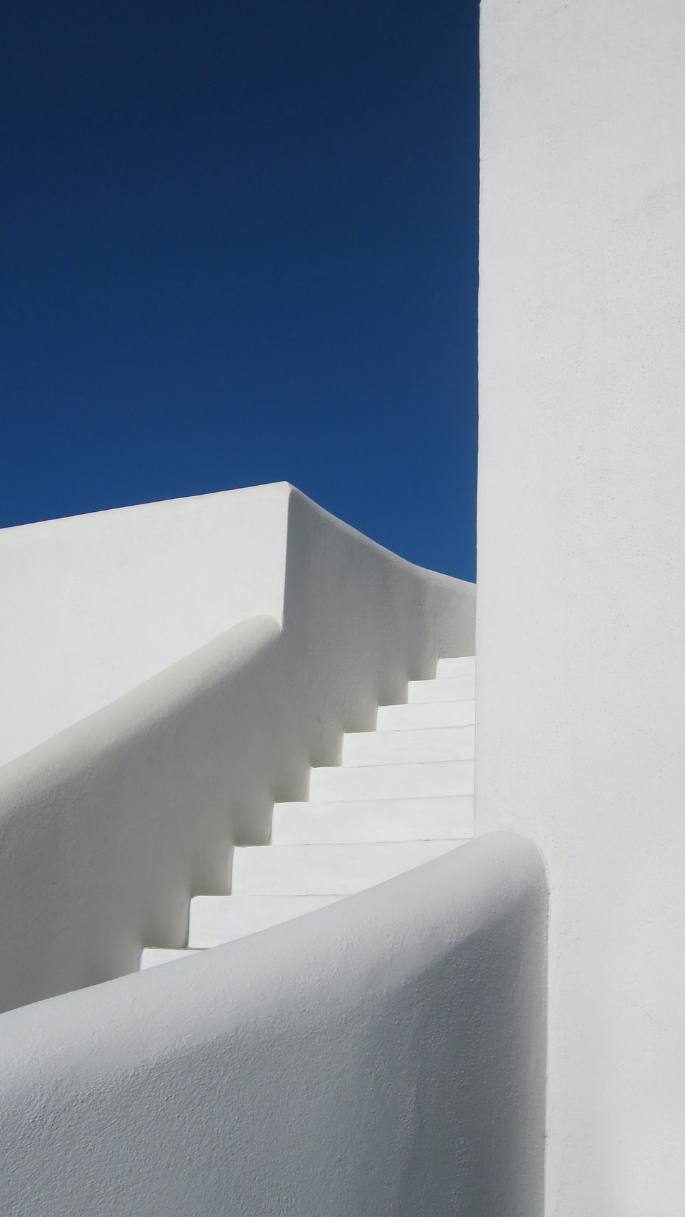 white concrete staircase under blue sky during daytime
