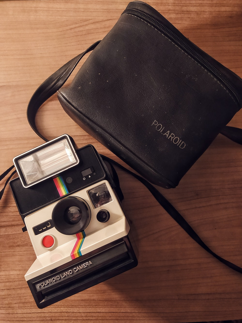black and white polaroid camera beside black leather bifold wallet