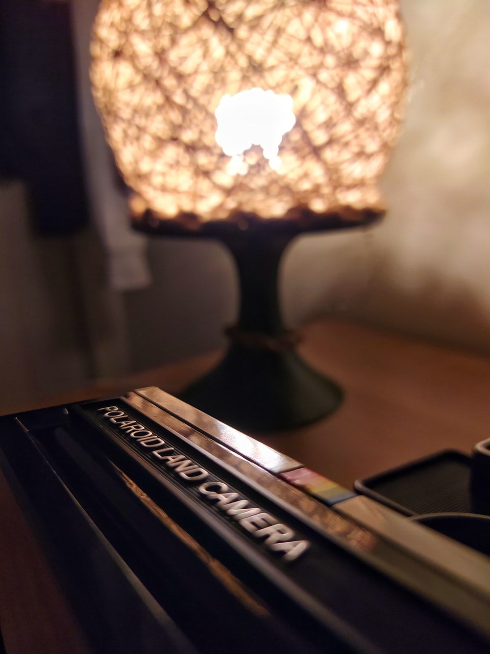 black and brown table lamp turned on on brown wooden table