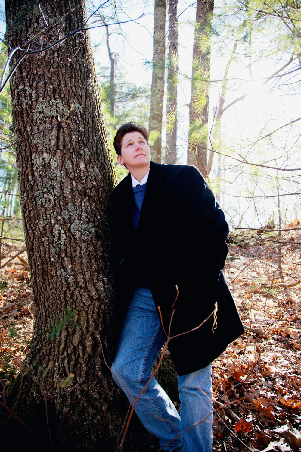 man in black coat and blue denim jeans sitting on tree