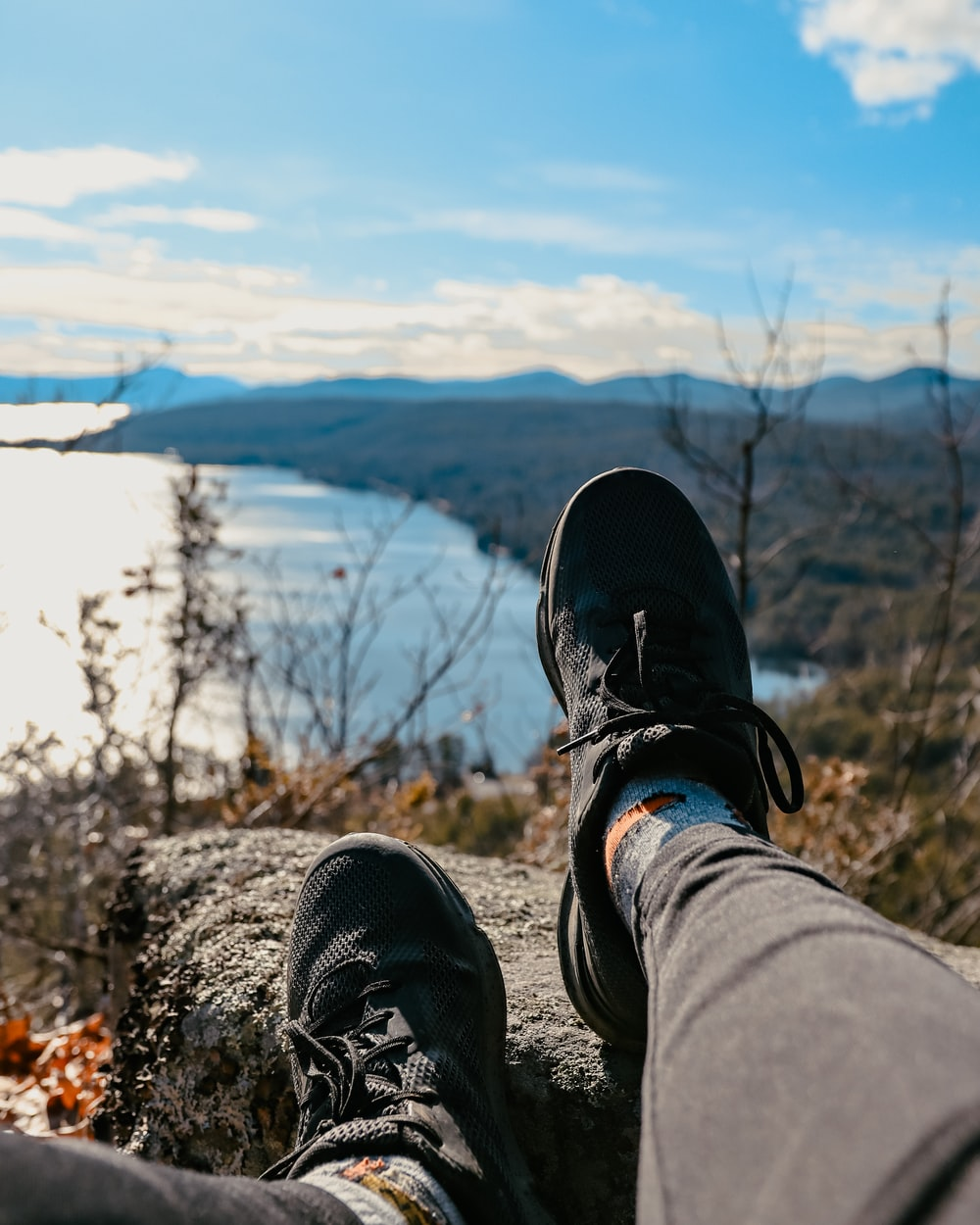 person in black and white sneakers sitting on rock