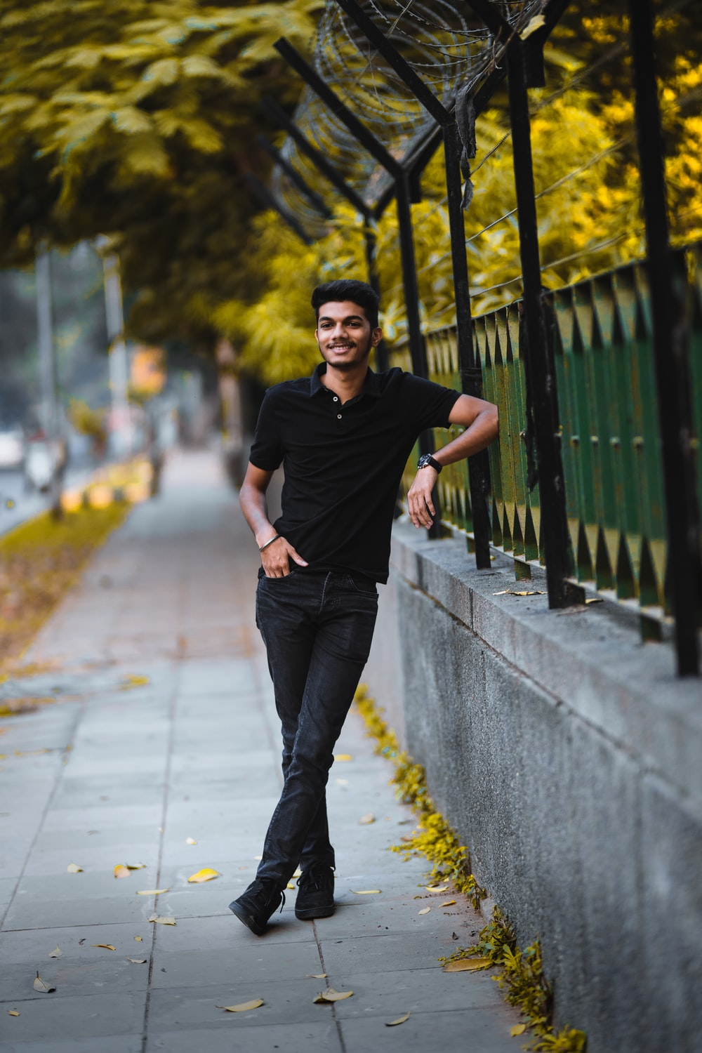 man in black crew neck t-shirt and blue denim jeans standing on gray concrete pathway