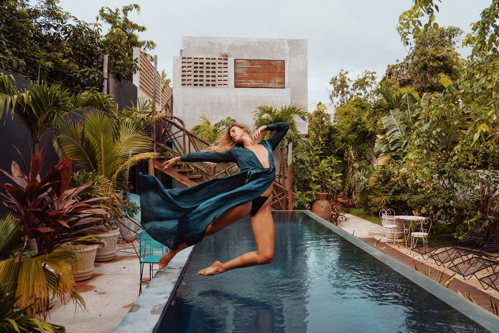 woman in blue dress sitting on swimming pool during daytime