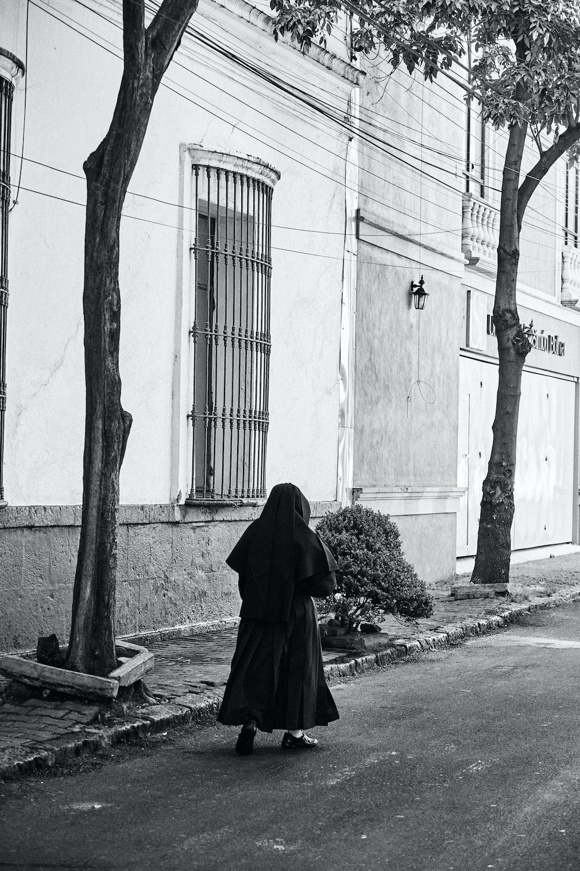person in black robe standing on sidewalk during daytime
