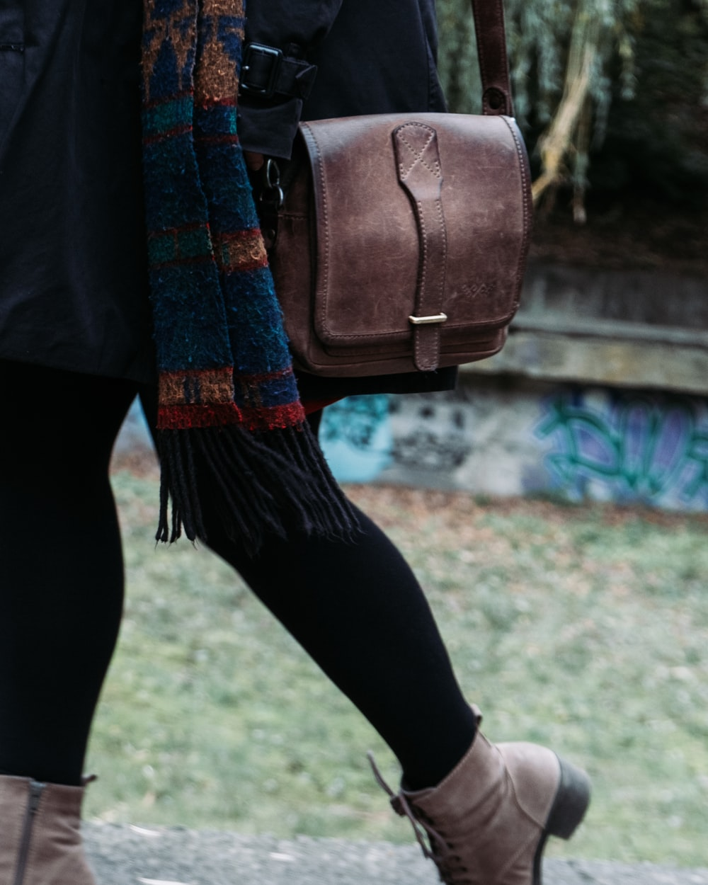 woman in black pants and brown leather sling bag