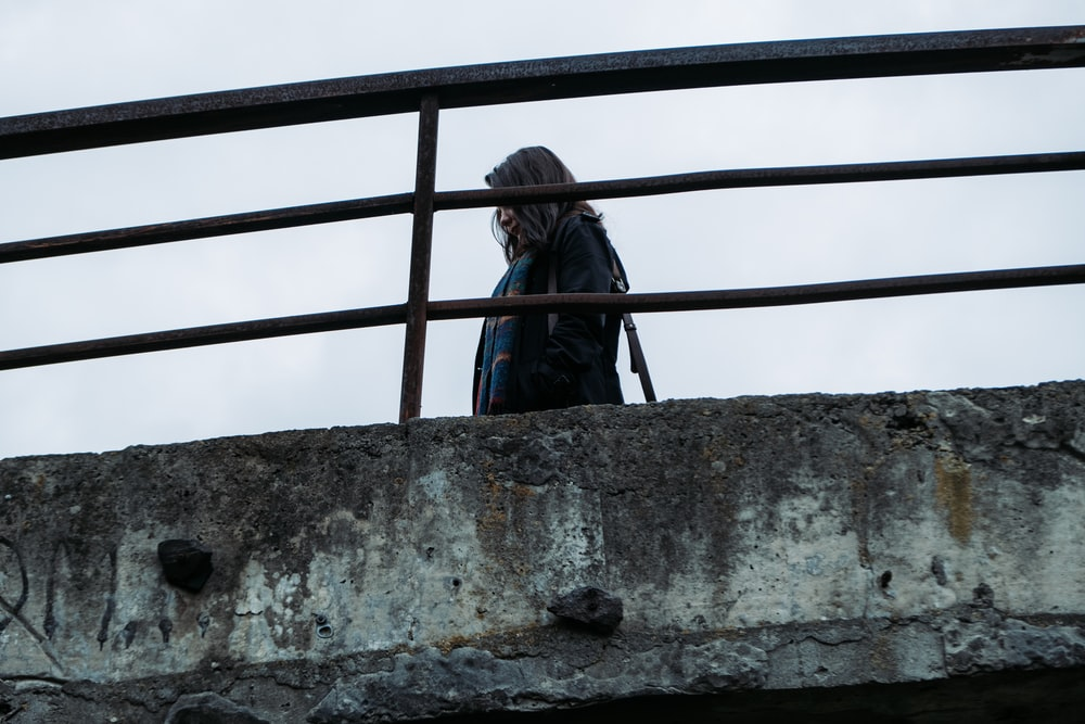 woman in blue jacket standing on gray concrete wall during daytime