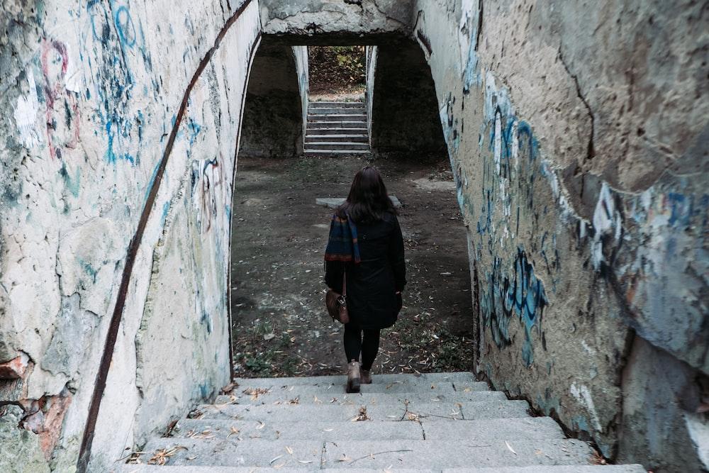 woman in black jacket walking on hallway
