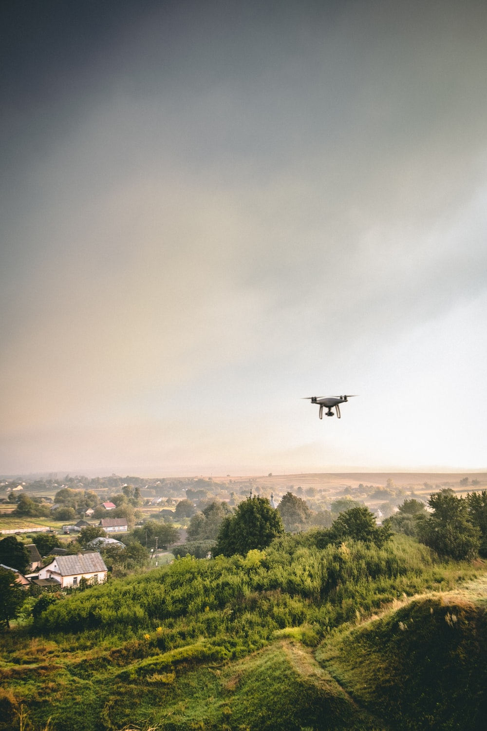 black drone flying over green trees and buildings during daytime