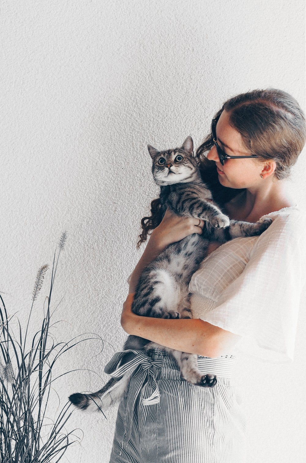 woman in black and white stripe shirt holding silver tabby cat
