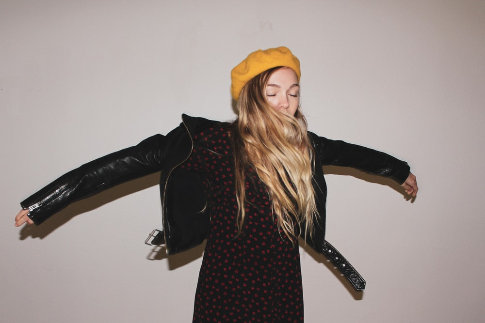woman in black long sleeve dress and yellow knit cap