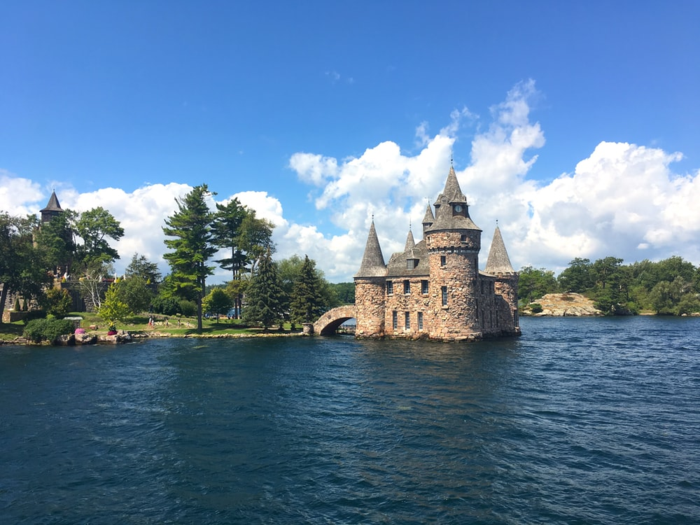 brown concrete castle near body of water under blue sky during daytime