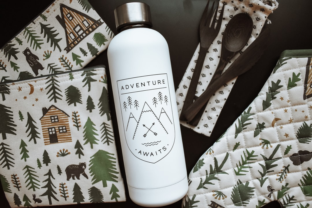 Adventure Awaits Water Bottle Flatlay With Rustic Cabin Themed Kitchen and Camping Products and Wooden Utensils. - unsplash