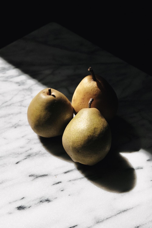 three yellow round fruits on white textile