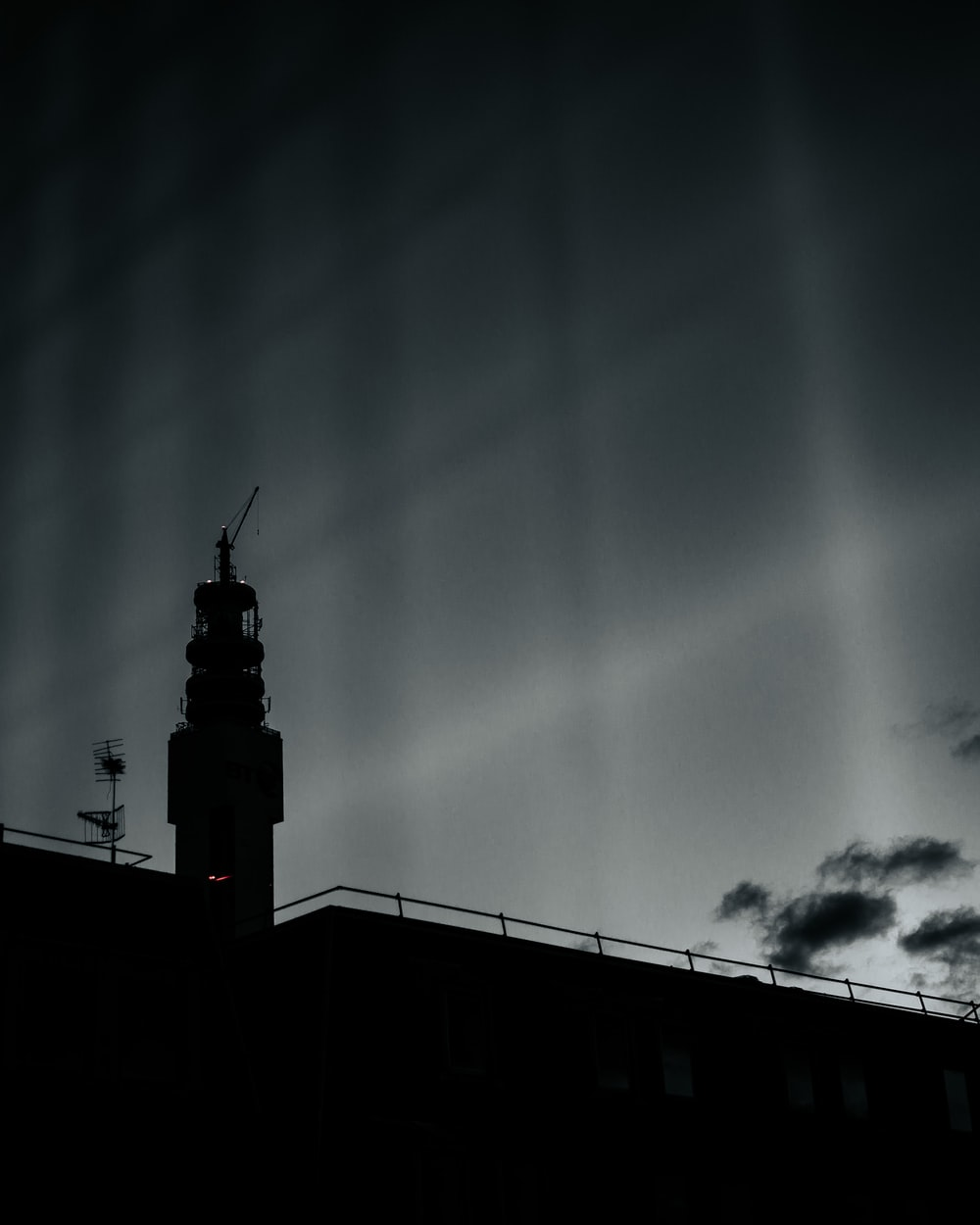 silhouette of tower under cloudy sky