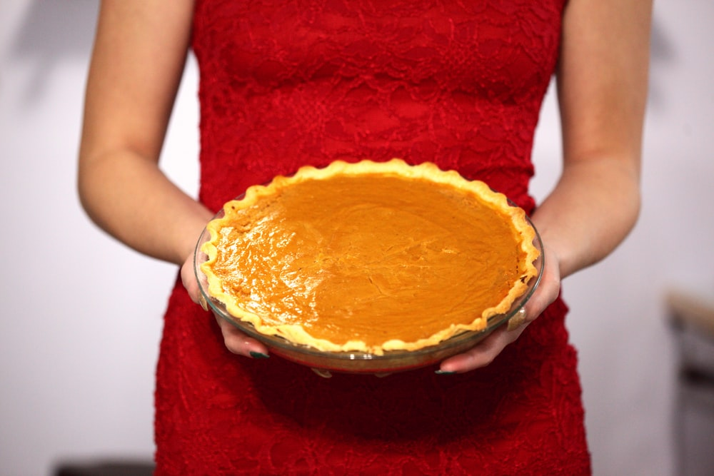 woman in red sleeveless dress holding pie
