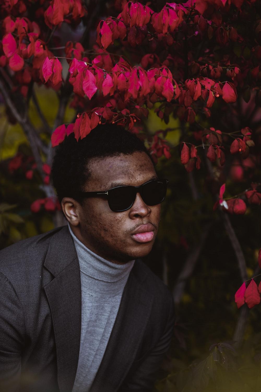man in black suit wearing black sunglasses standing near pink flowers