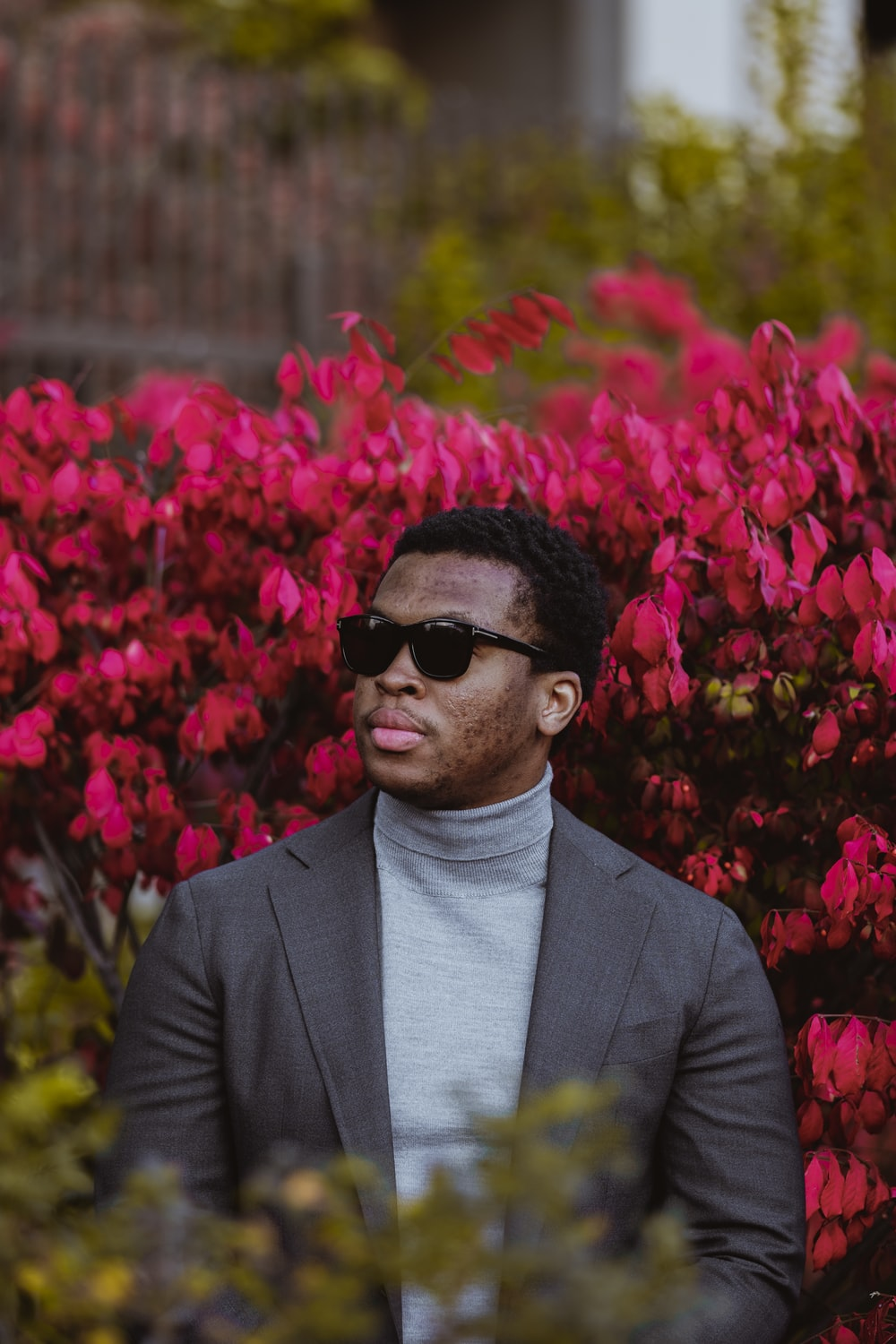 man in black suit standing near red flowers