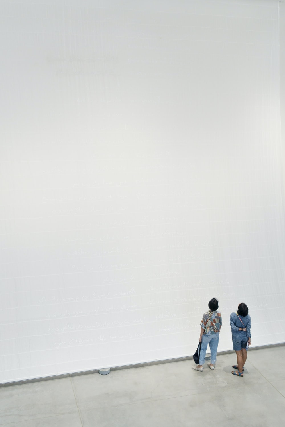3 men and 2 women standing on white wall
